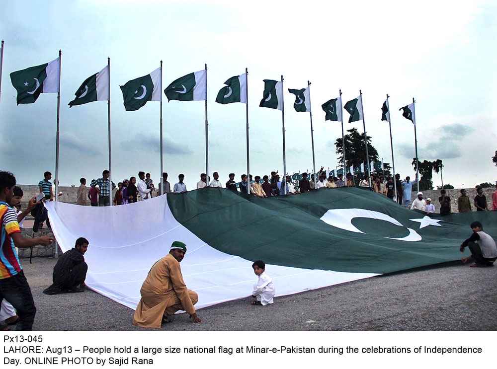 People hold a large size national flag at Minar-e-Pakistan
