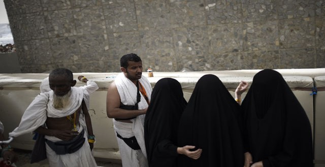 "Muslim pilgrims throw pebbles at pillars during the ""Jamarat"" ritual, the stoning of Satan, in Mina near the holy city of Mecca, on September 24, 2015. Pilgrims pelt pillars symbolizing the devil with pebbles to show their defiance on the third day of the hajj as Muslims worldwide mark the Eid al-Adha or the Feast of the Sacrifice, marking the end of the hajj pilgrimage to Mecca and commemorating Abraham's willingness to sacrifice his son Ismail on God's command in the holy city of Mecca. AFP PHOTO / MOHAMMED AL-SHAIKH"